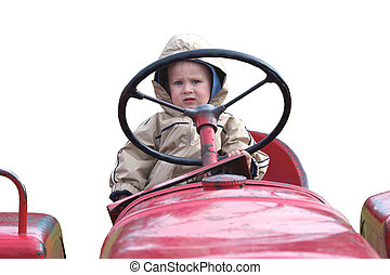 Little boy behind the wheel of a Tractor