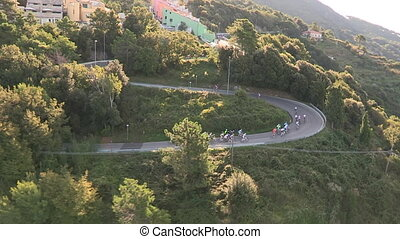 Cyclists race along a winding road