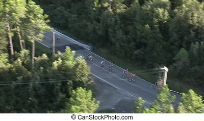 Cyclists speedily race on a downwards slope