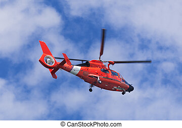 Red rescue helicopter moving in blue sky with blur propeller...