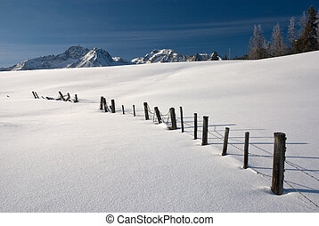 Idaho Mountains winter - Barbed Wire fence covered with snow...