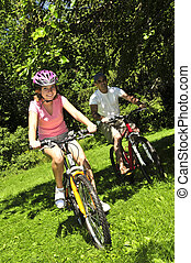 Family riding bicycles - Teenage girl and her father riding...
