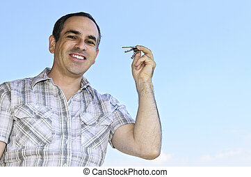 Man holding keys - Smiling man holding house keys on blue...