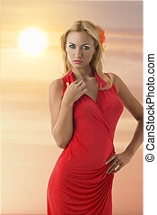 pretty blonde girl with pink dress looks in to the lens