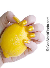 hands with yellow varnish are holding a lemon - Womens hands...