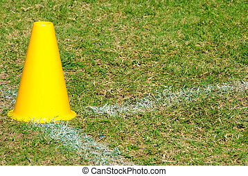 Yellow cone on grass field - Yellow cone on a grass football...
