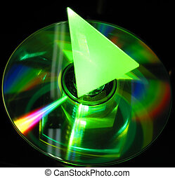 glass prism on a CD lit up by a gre - reflection of a glass...