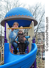 Mom and son on the playground - In the spring, a 2-year-old...