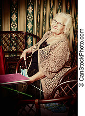 cozy home - Portrait of a smiling senior woman reading a...
