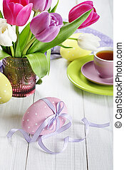 tulips and easter eggs - Pink, violet and white tulips in a...