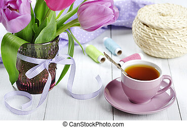 Cup of tea with tulips bouquet in glass vase on white wooden...