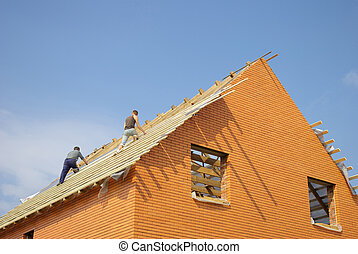 roof - Construction workers placing the first section of...