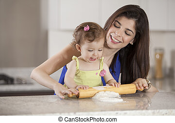 Helping mom cook dinner - Cute baby girl and her mother...