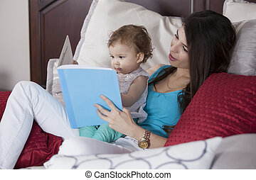 Reading a bedtime story - Young mother reading a story to...