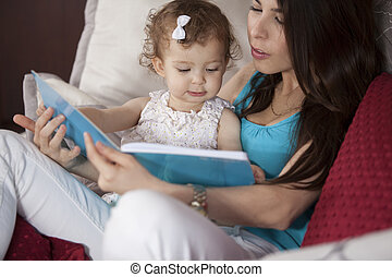 Once upon a time... - Young mother reading a story to her...