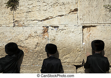Three orthodox Jewish young adult pressed in prayer against...