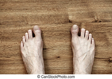 Man Feet on Parquet - Bare and somewhat hairy feet of an...