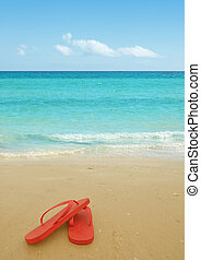 Red flip flops on the beach sand.Concept of summer vacations