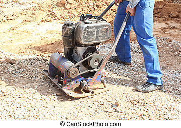 worker with hand compactor flat gravel and preparing for...