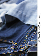 Jeans Background - Various pairs of jeans pants scattered in...