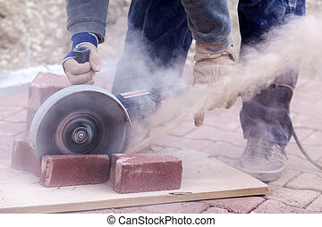 cutting pavers - worker uses a stone cutter to cut the brick...