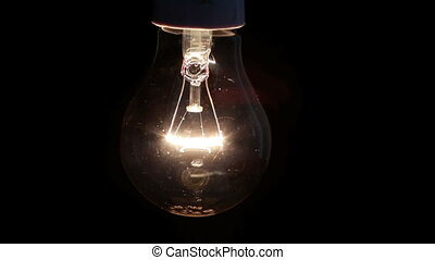 Light bulb swinging and turning off on black background