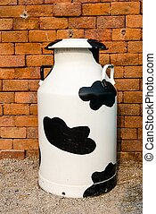 A large multi color metal milk container, taken on a sunny...