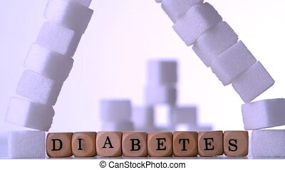 Wall of sugar cubes falling over dice spelling out diabetes...