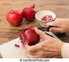 Cutting a pomegranate - Hands cutting a pomegranate in four...