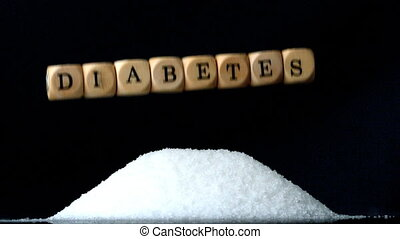 Dice spelling diabetes falling over a pile of sugar on black...