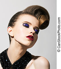 Imagination. Bright Young Woman with Blue Holiday Eye Makeup and Festive Hairstyle