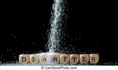 Sugar powder being poured over dice spelling out diabetes in...