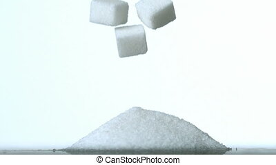 Sugar cubes falling into pile of su