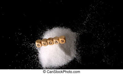 Dice spelling out sugar falling in