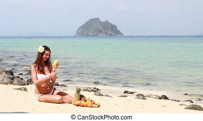 Young woman relaxing on beach and eating fruits
