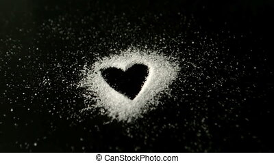 Heart drawn into sugar being blown out by wind in slow...