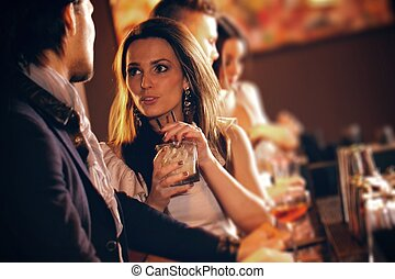 Young Woman in Conversation with a Guy at the Bar - Young...