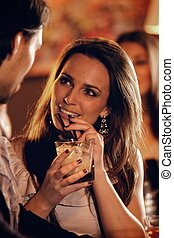 Beautiful Woman at the Bar Talking with a Guy - Closeup of a...