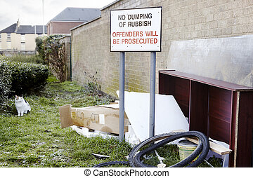 Abandoned garbage left next to no dumping sign