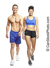 Young man and woman walking in sports outfits on white...
