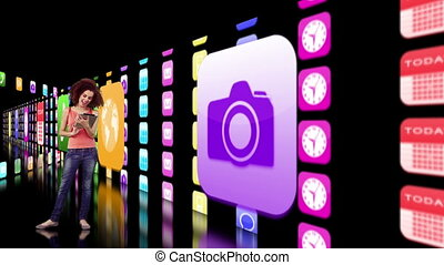 Woman using tablet with application icons projected on black...
