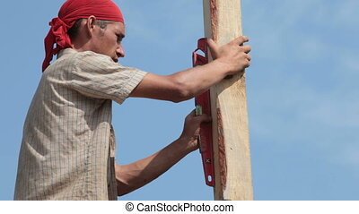 Roofer working - Construction worker using level tube at...