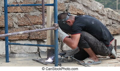Roofing work - welding piles - worker with protective mask...
