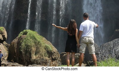 Couple contemplating a tropical waterfall