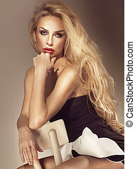 Beautiful elegant blonde woman sitting on chair. Long...