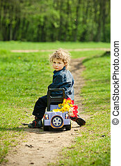 little boy on a toy-car in park