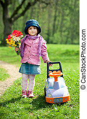 beautiful little girl with car in park