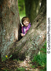 little girl climbing tree in the park