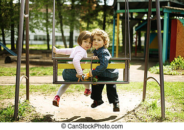 boy and girl on the swings
