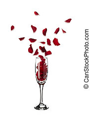Red rose petals popping out of champagne glass into the air